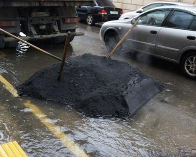 Севастопольские дорожники совсем не оригинальные – латают ямы в дождь (фото)