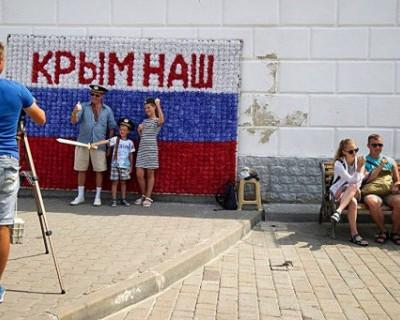 Киевлянка в Севастополе развернула украинский флаг и стала просить горожан сфотографировать её с этим трофеем