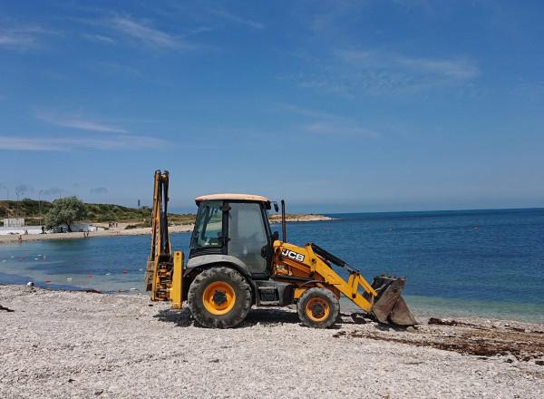убирают водоросли на пляже